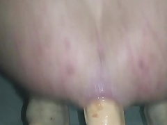 Bouncing on a huge dildo