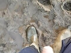 Walking in mud wearing dirty worker gear and rubber boots